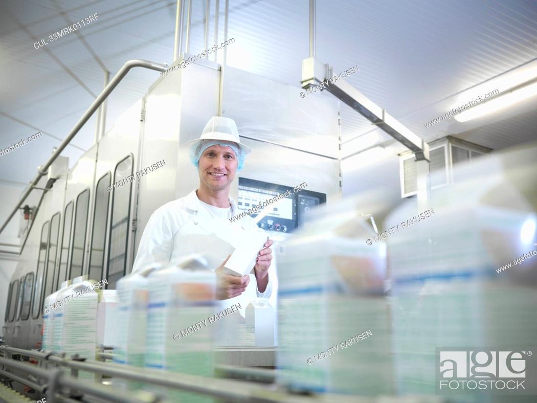 Stock Photo: Worker inspecting goat's milk in dairy.