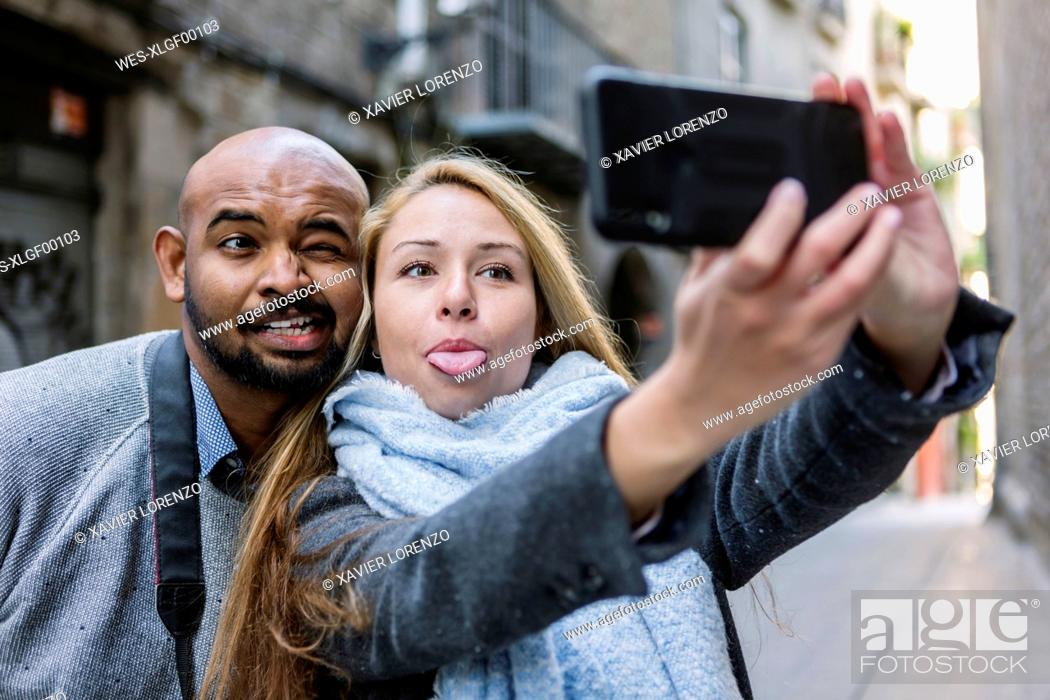Stock Photo: Portrait of couplepulling faces while taking selfie with smartphone, Barcelona, Spain.