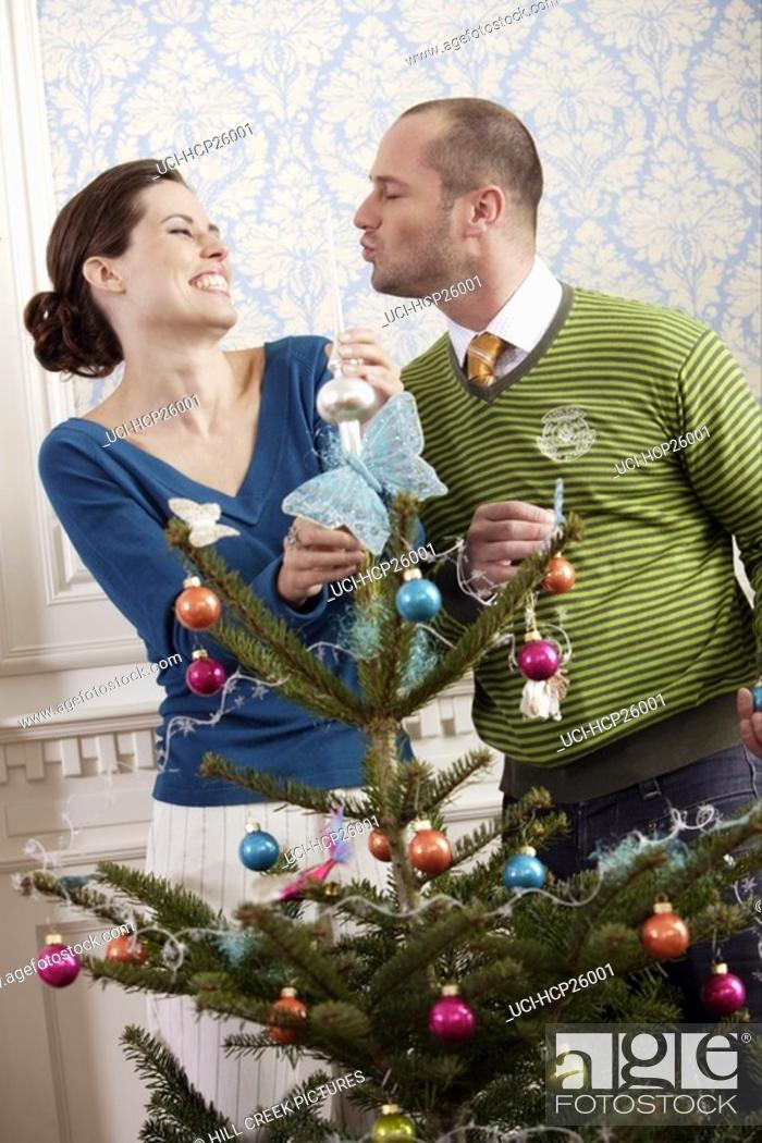Stock Photo: Couple decorating a Christmas tree.