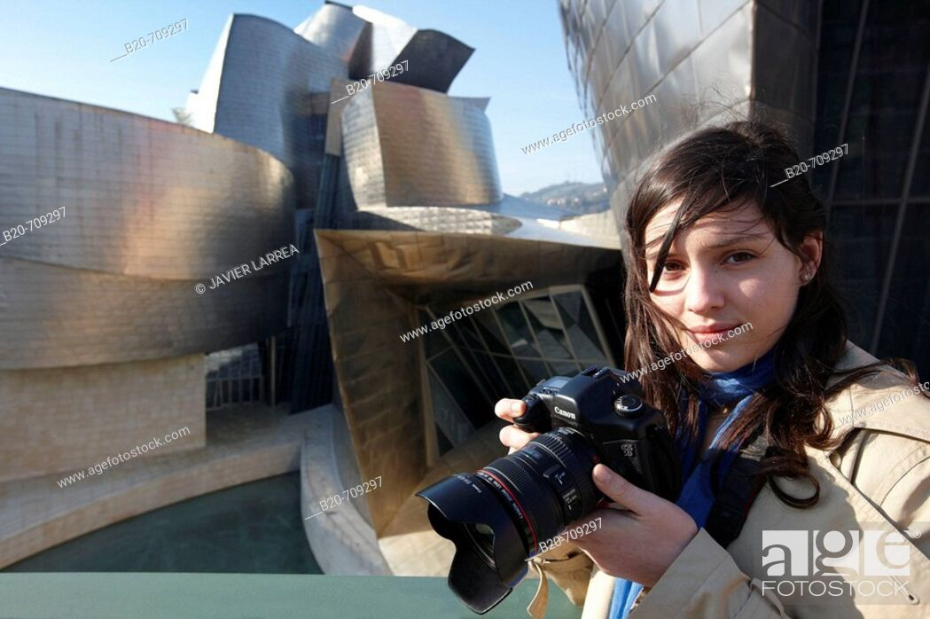Stock Photo: Young woman with camera in front of the Guggenheim Museum, Bilbao. Biscay, Euskadi, Spain.
