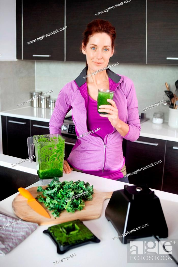 Stock Photo: Mature woman with glass of fresh vegetable juice.