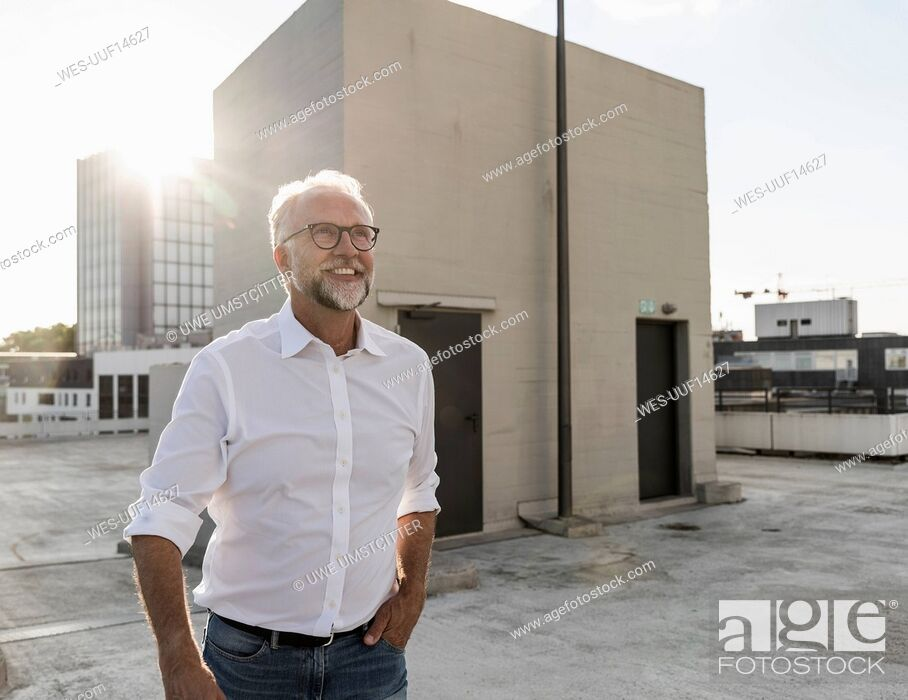 Stock Photo: Mature man standing on roof of a high-rise building, looking up, smiling.