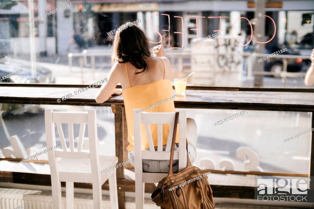 Stock Photo: Woman sitting in cafe, writing the word 'coffee' on window pane.