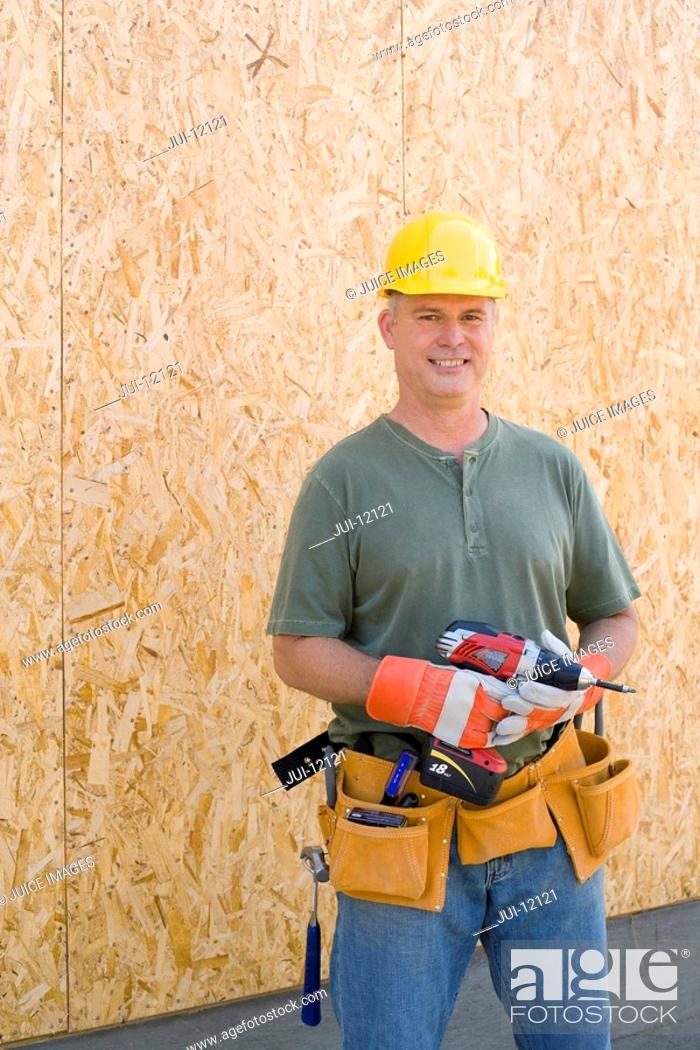 Stock Photo: Male builder in hardhat with electric drill, smiling, portrait.