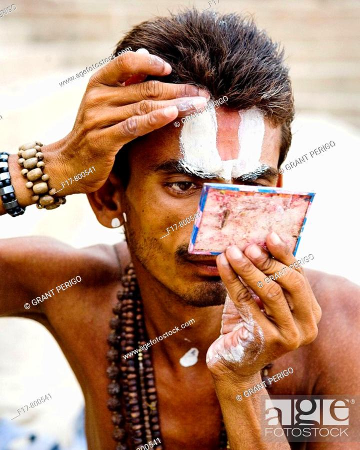 Stock Photo: picture of a priest applying makeup by the ganges river.