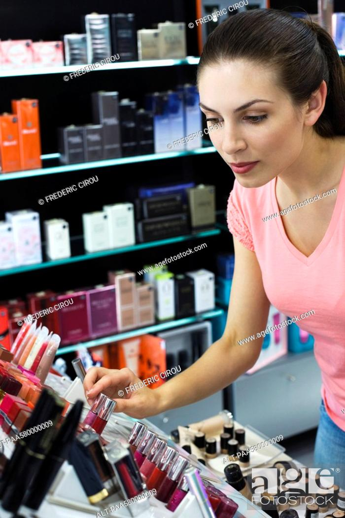 Stock Photo: Young woman browsing cosmetics in store.