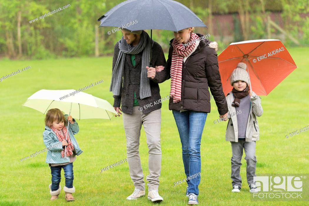 Stock Photo: Family with umbrellas in a park.