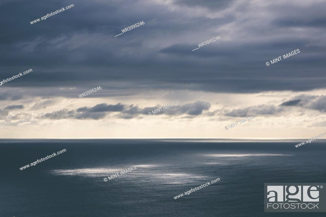 Photo de stock: Storm clouds clearing over expansive ocean, dappled sunlight on water, northern Oregon coast.