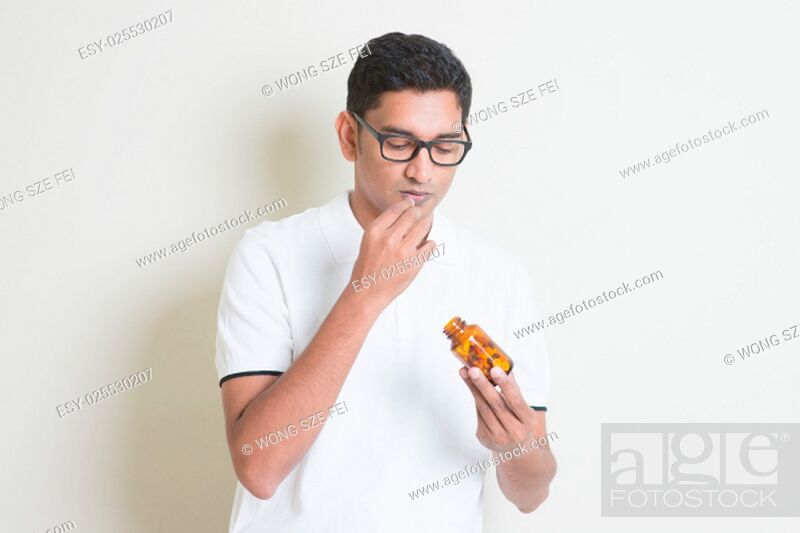 Stock Photo: Sick Indian guy eating medicine pill. Asian man standing on plain background with shadow and copy space.