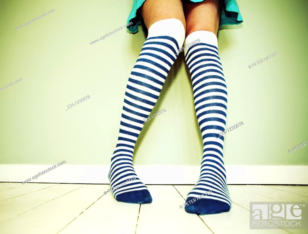 Stock Photo: Adult female wearing stripey socks stands against a wall on a wooden floor painted white.