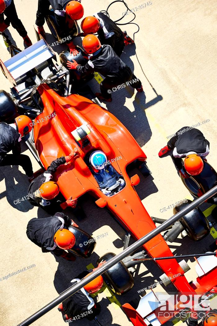 Stock Photo: Overhead pit crew replacing tires on formula one race car in pit lane.