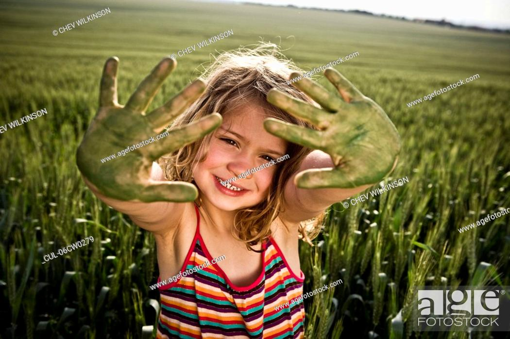 Stock Photo: Girl with painted green hands.
