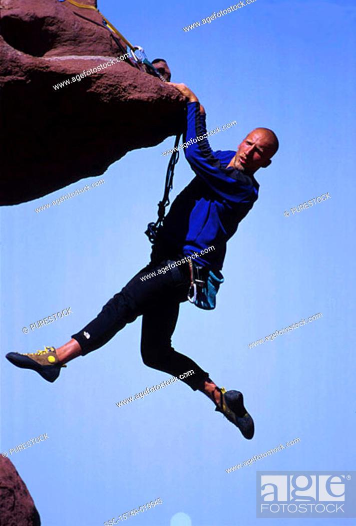 Stock Photo: Young adult man mountain climbing, Utah, USA.