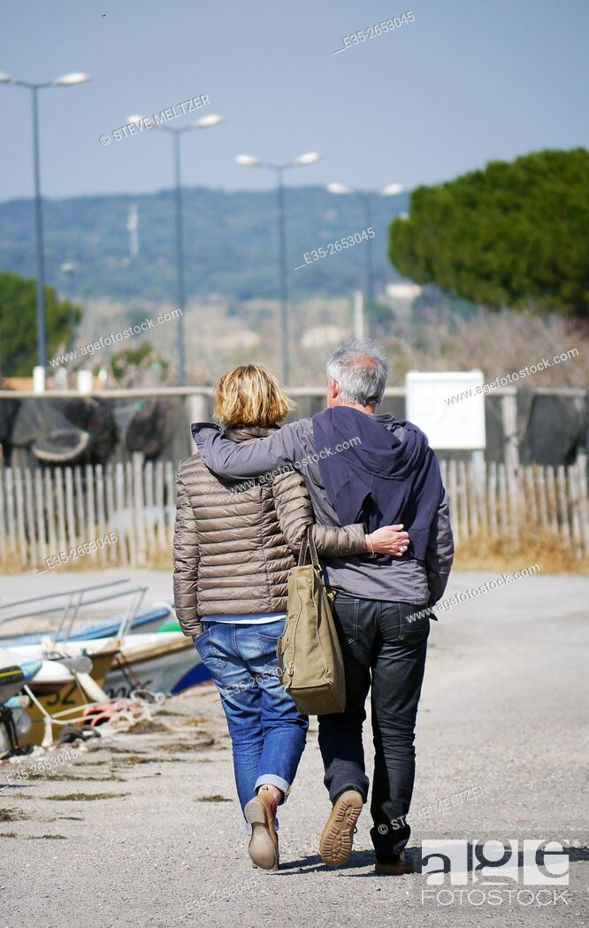 Stock Photo: A couple pass a quiet moment walking along the beach trail in Meze, France.