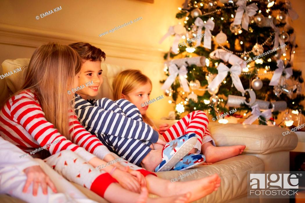 Stock Photo: Boy and girls in striped pyjamas on sofa at christmas.