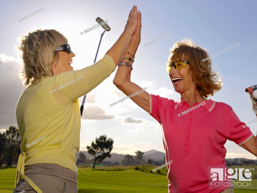 Stock Photo: Women golfers doing a high five.