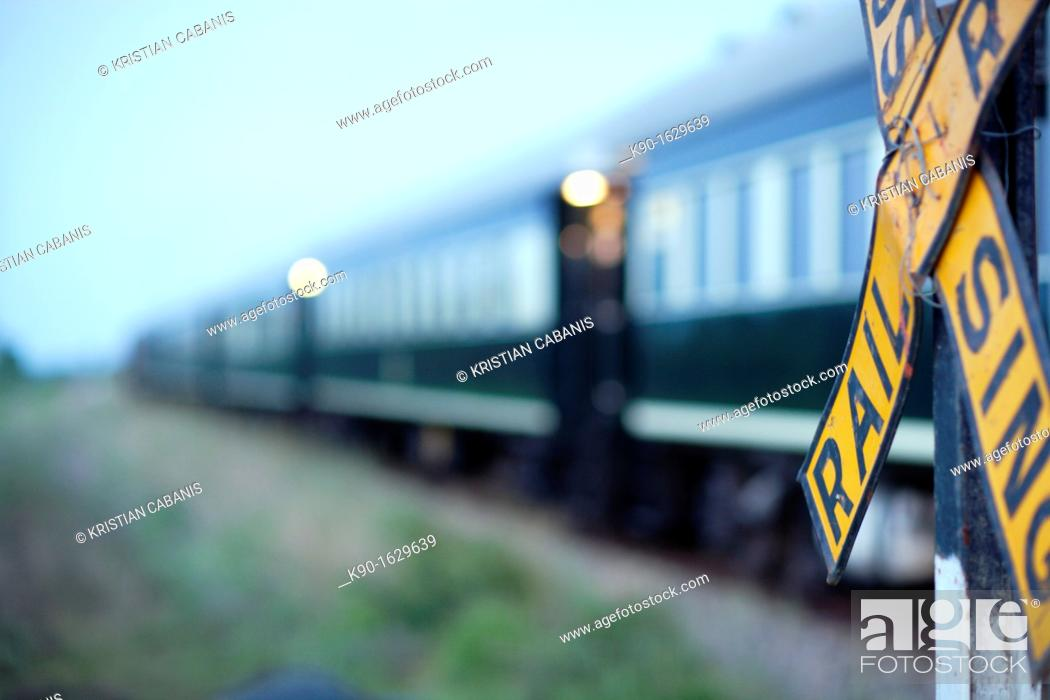 Stock Photo: Blurred Rovos Rail passenger train passing by a Railroad Crossing, with the yellow warning sign about trains in the foreground, Southern Africa, Botswana.