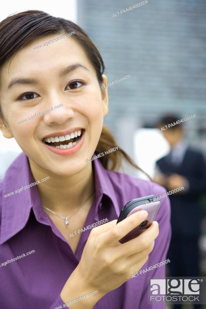 Stock Photo: Young woman holding cell phone, laughing.