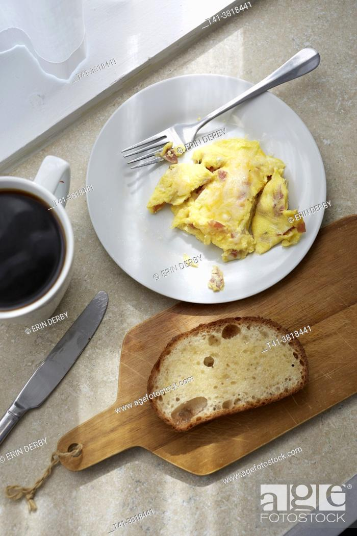 Stock Photo: A kitchen counter with scrambled eggs, toast, coffee, and streaks of sunlight.