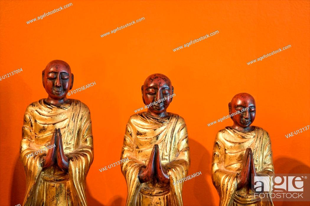 Stock Photo: Three wooden statues of Buddhist disciples against orange wall.