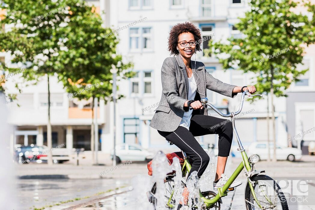 Stock Photo: Portrait of smiling woman on bicycle.