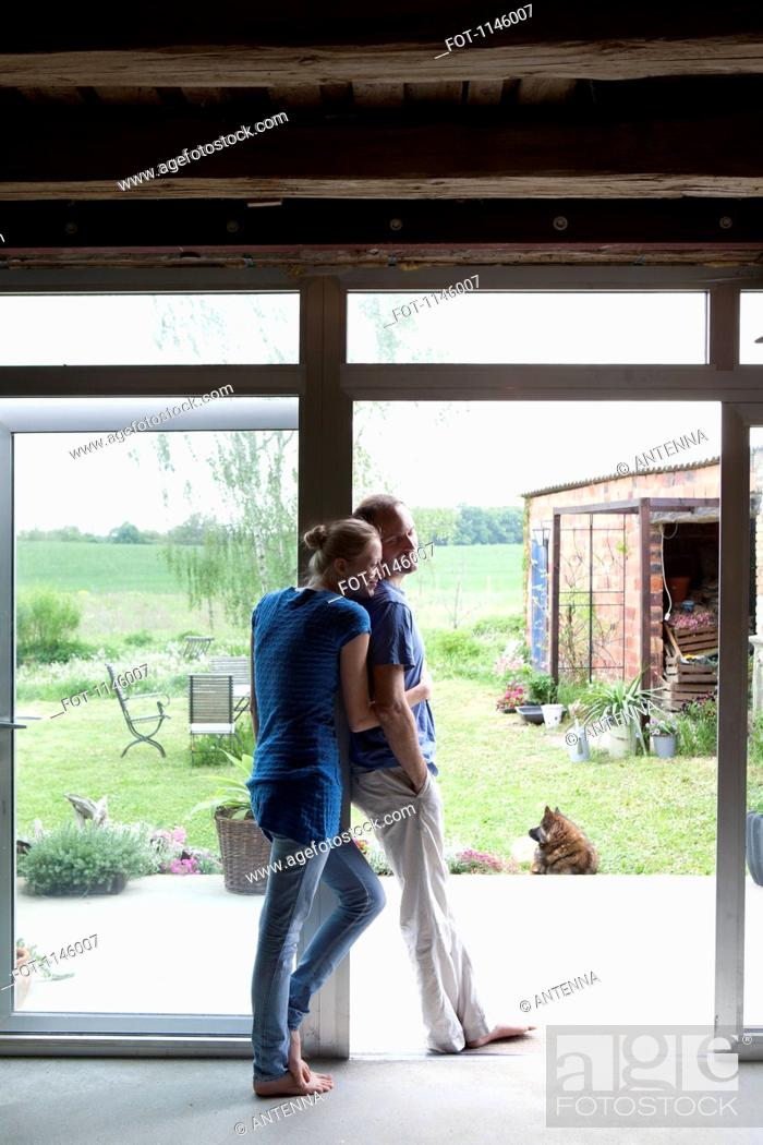 Stock Photo: An affectionate couple leaning in the doorway of their house.