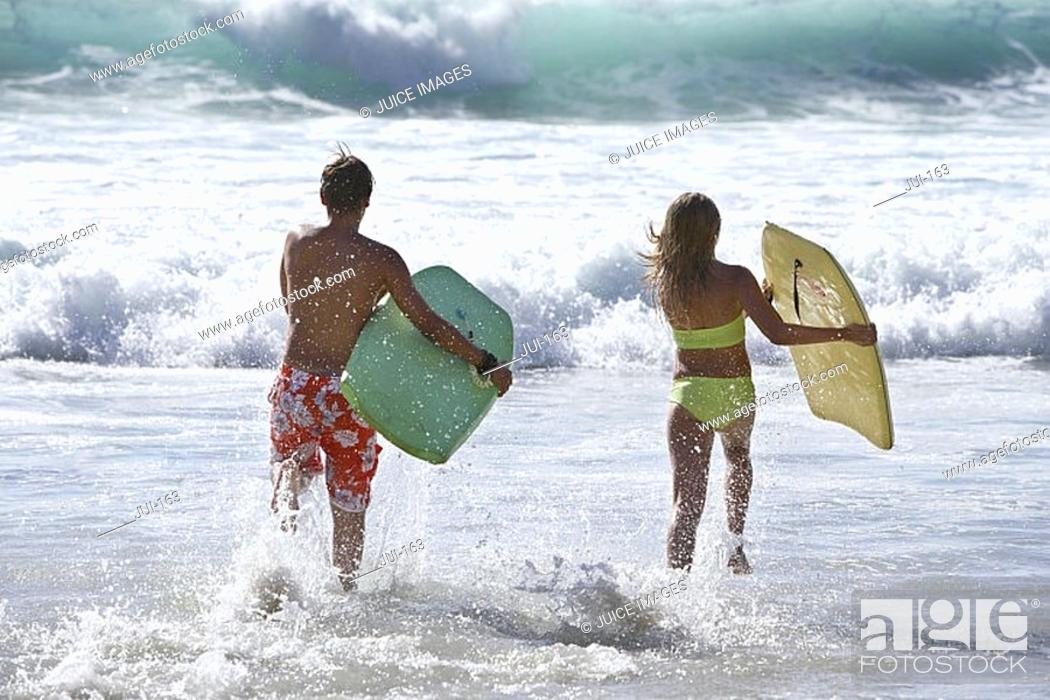 Stock Photo: Two teenage 13-15 bodysurfers running into surf, carrying bodyboards, side by side, rear view.