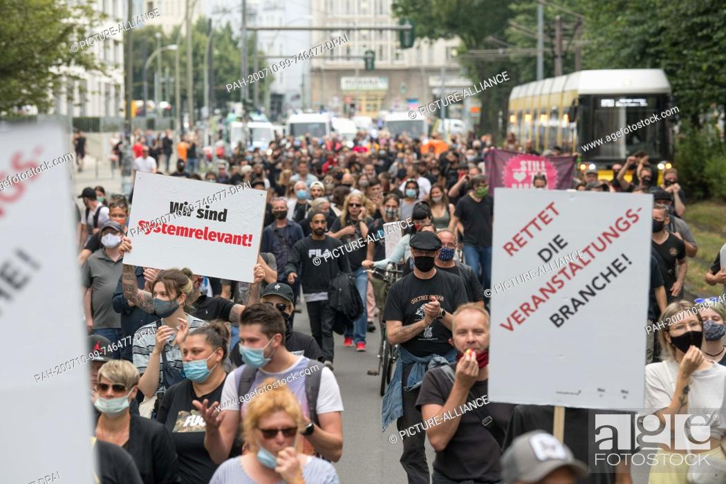 """Stock Photo: 10 July 2020, Berlin: """"""""We are system relevant"""""""" and """"""""Save the event industry"""""""" are written on posters that are displayed by participants at a demonstration of."""