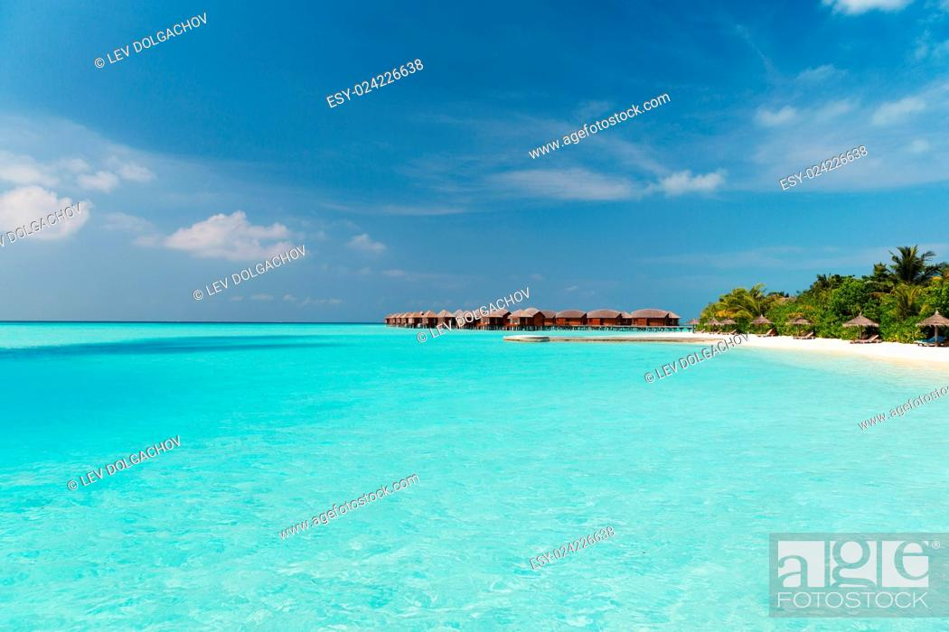 Stock Photo: travel, tourism, vacation and summer holidays concept - bungalow huts in sea water on exotic resort beach.