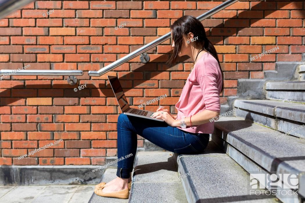 Stock Photo: Woman sitting on stairs working with laptop.