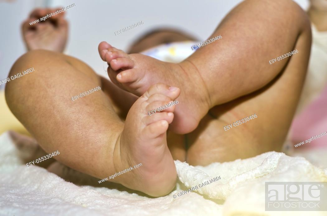 Stock Photo: Changing the diaper to the baby, detail on the legs and feet.