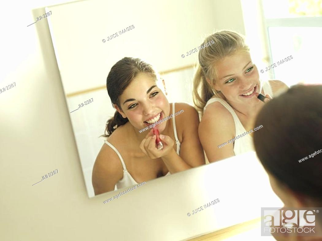 Stock Photo: Teenage girls 15-17 looking at reflection in mirror, applying make-up, smiling, rear view tilt.