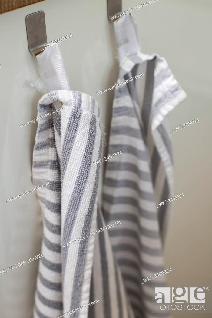 Imagen: Two kitchen towels hanging on a hooks in a kitchen close-up modern.
