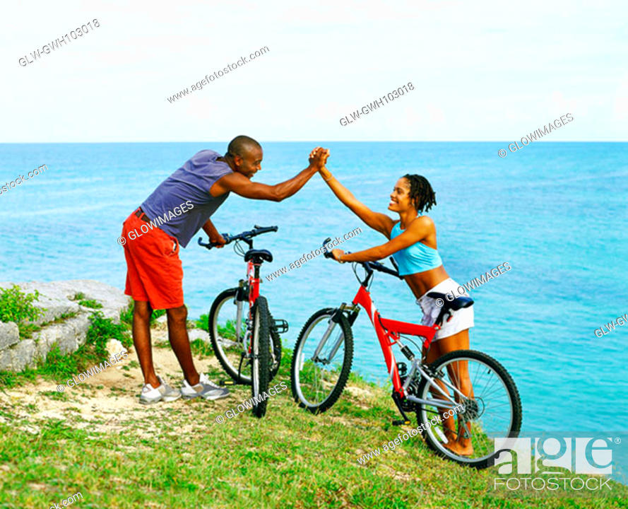 Stock Photo: Side profile of a young couple holding hands near bicycles, Bermuda.