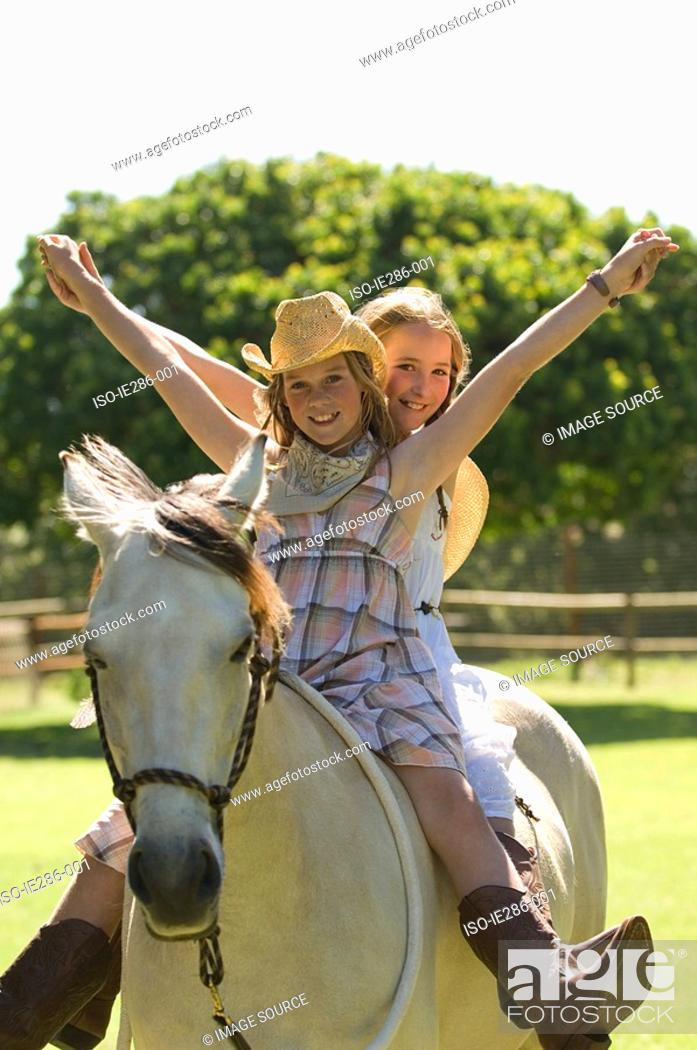 Stock Photo: Two girls riding a horse.