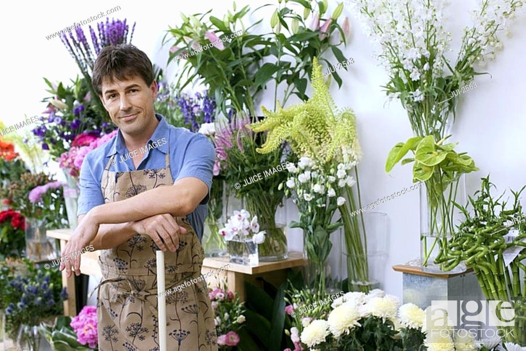 Stock Photo: Male florist in apron standing in flower shop, leaning on broom beside display, smiling, portrait.
