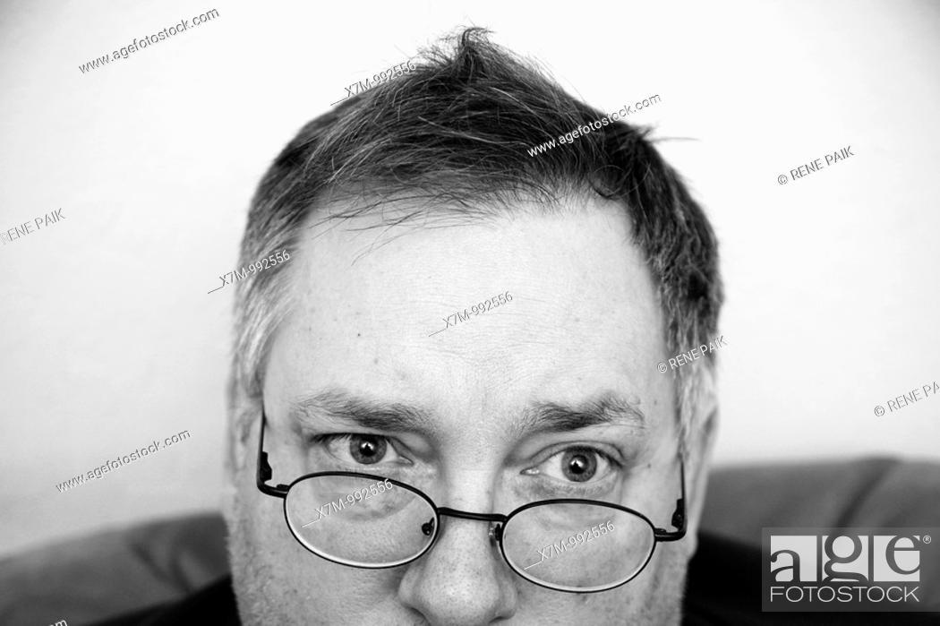 Stock Photo: Man quizzically peering over his eyeglasses.