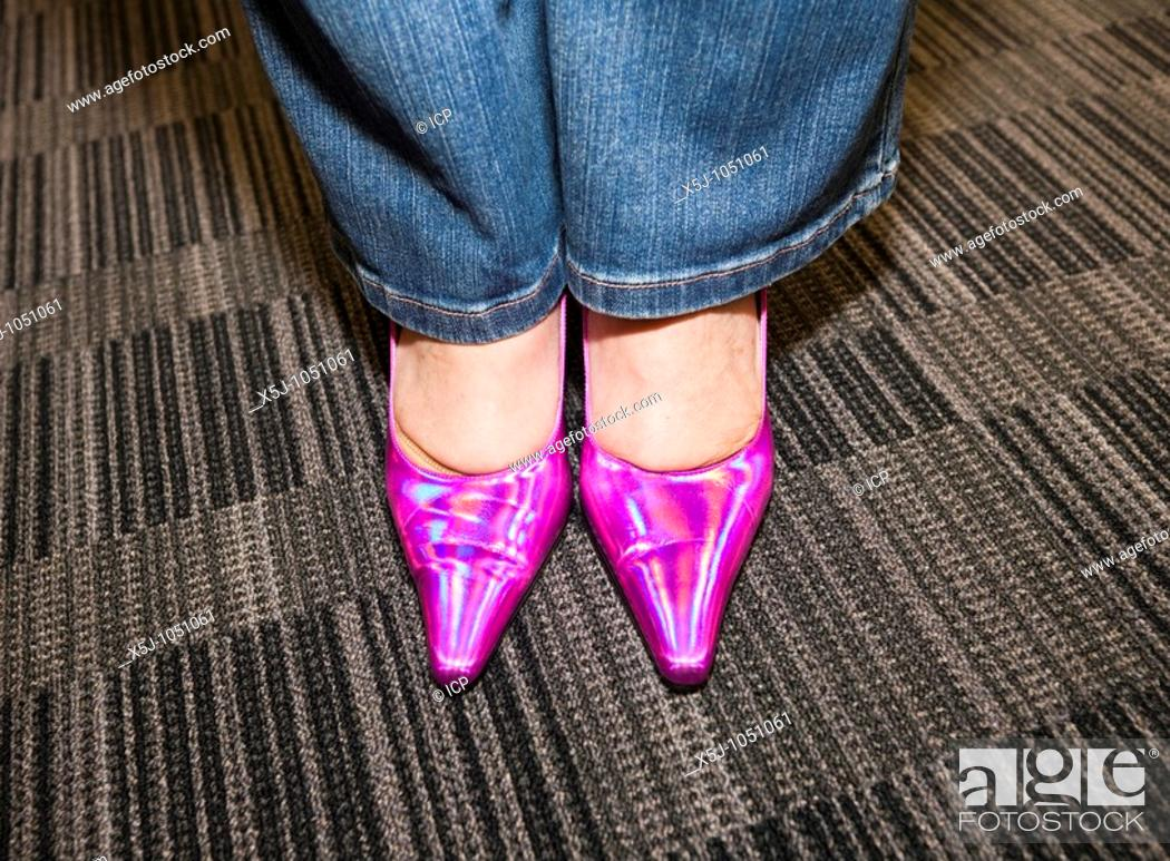Stock Photo: Woman wearing pink shoes for work on 'Dare to wear it' Pink day in aid of Breast Cancer Research UK.