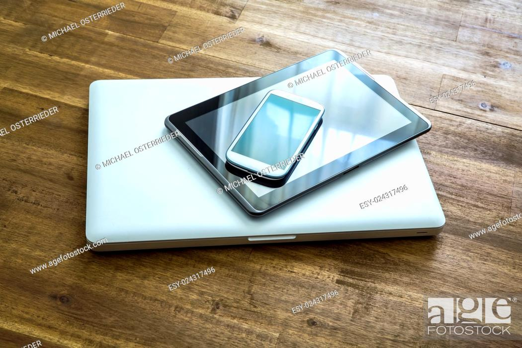 Stock Photo: A Laptop computer, a Tablet PC and a Smartphone on a wooden Desktop. . .