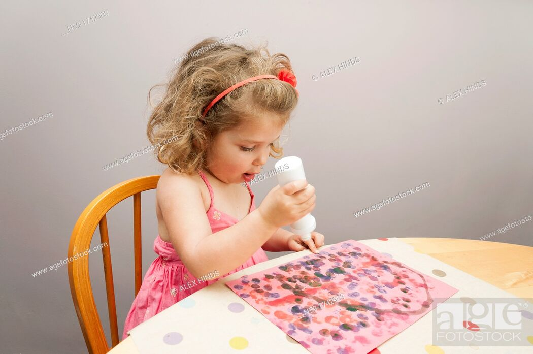 Stock Photo: Three year old girl painting a dot picture.