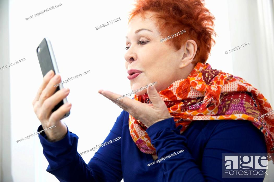 Stock Photo: Older Caucasian woman blowing kiss at cell phone.