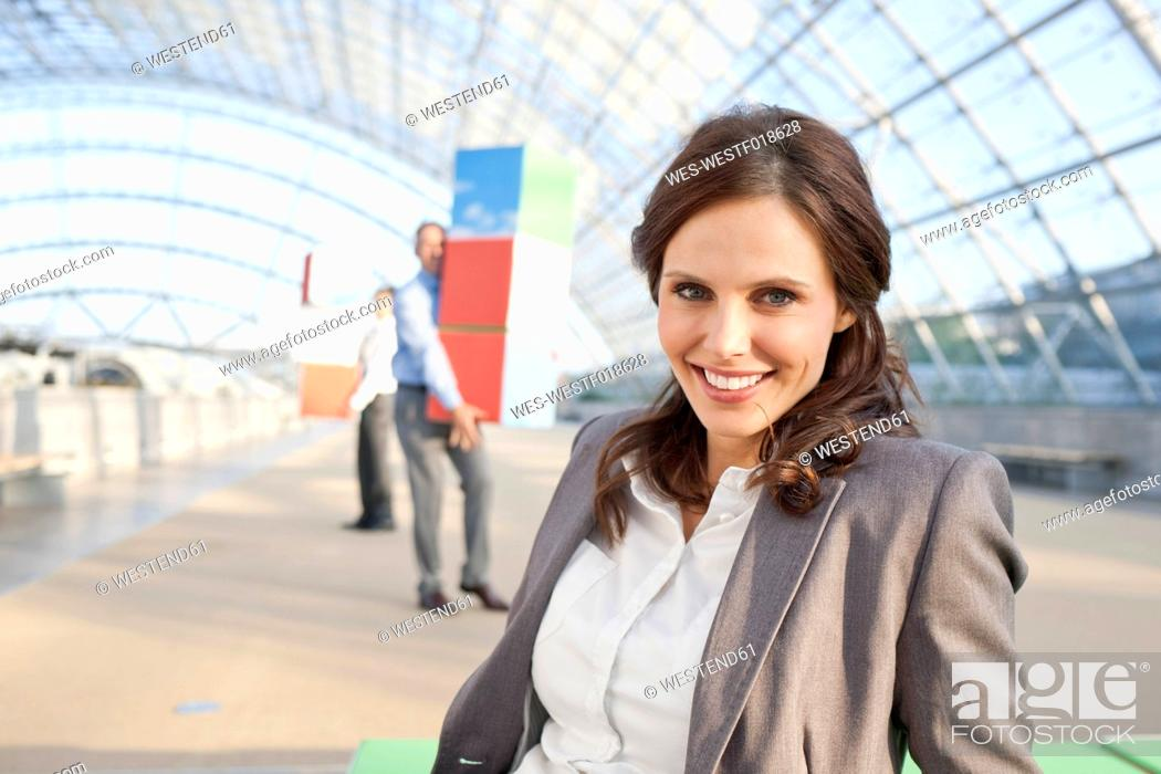 Stock Photo: Germany, Leipzig, Businesswoman smiling with businessman in background.