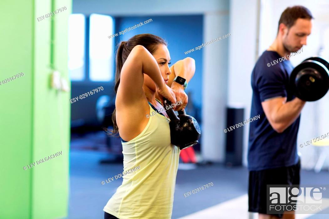 Stock Photo: sport, fitness, lifestyle and people concept - woman with kettlebell and man with dumbbell exercising in gym.