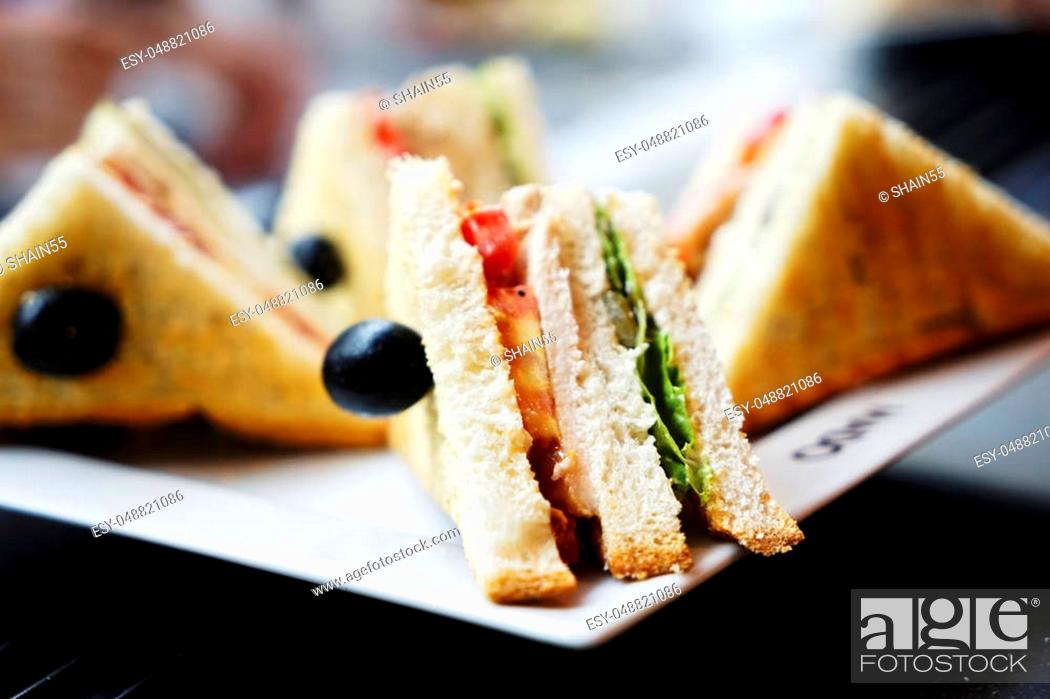 Stock Photo: sandwiches and burgers with meat, cheese and greens on a white plate.