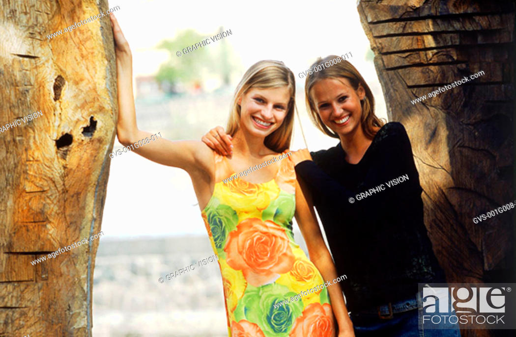 Stock Photo: Portrait of two young women standing by a wall.