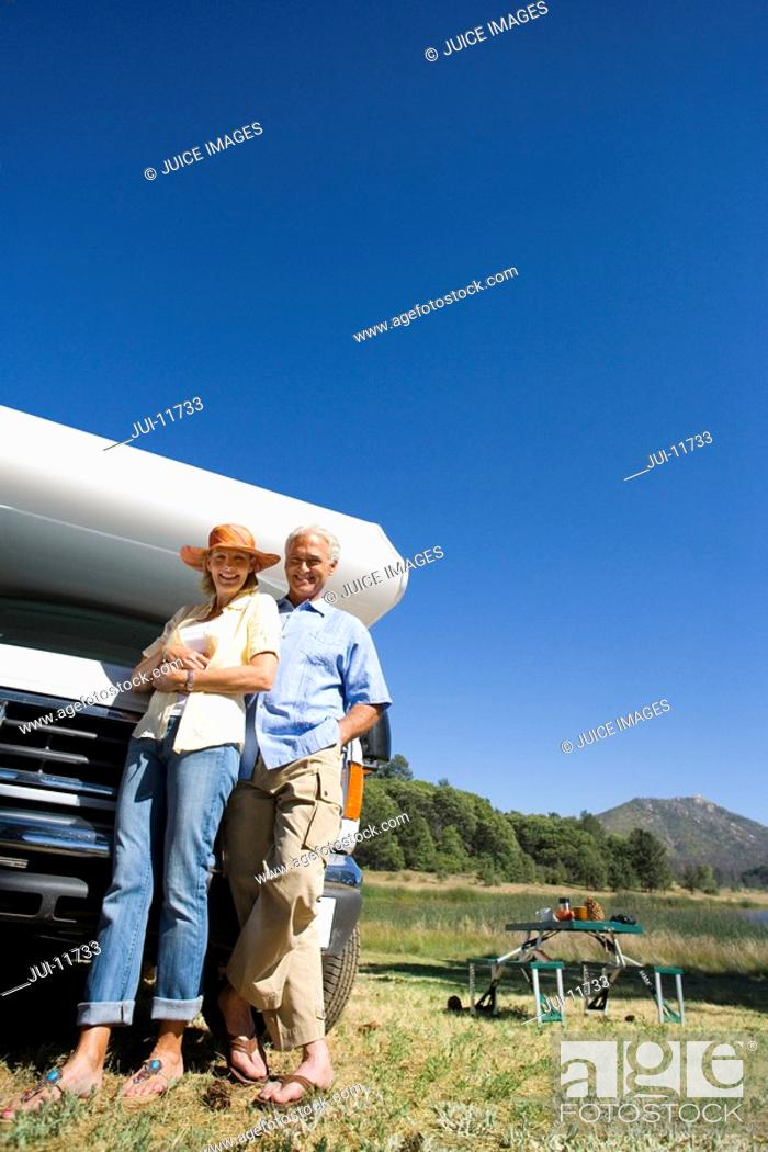 Stock Photo: Mature couple by motor home and portable picnic table, smiling, portrait, low angle view.
