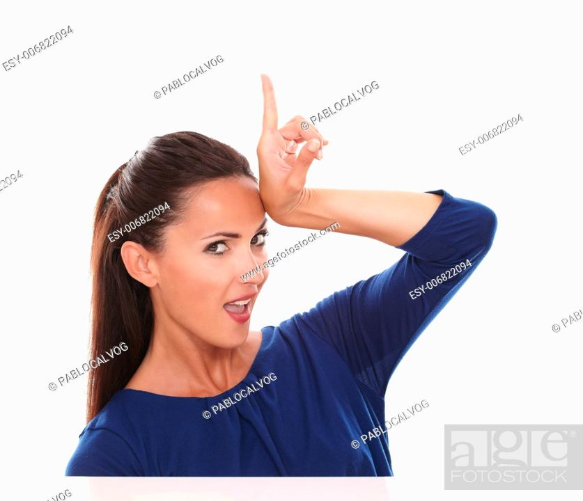Stock Photo: Pretty lady in blue blouse pointing up while looking at you in white background - copyspace.