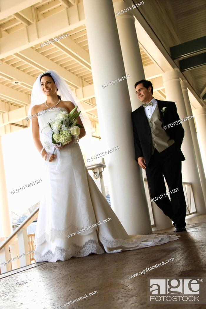 Stock Photo: Caucasian mid-adult fbride and groom standing on porch.