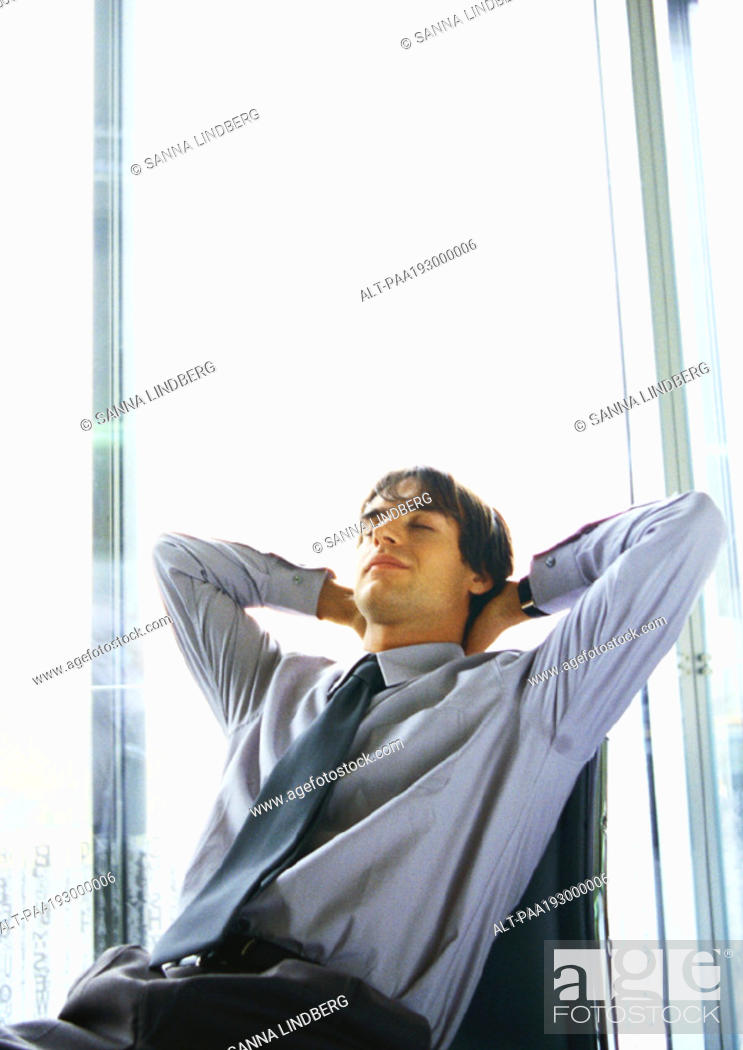 Stock Photo: Man leaning back in chair, hands behind head.