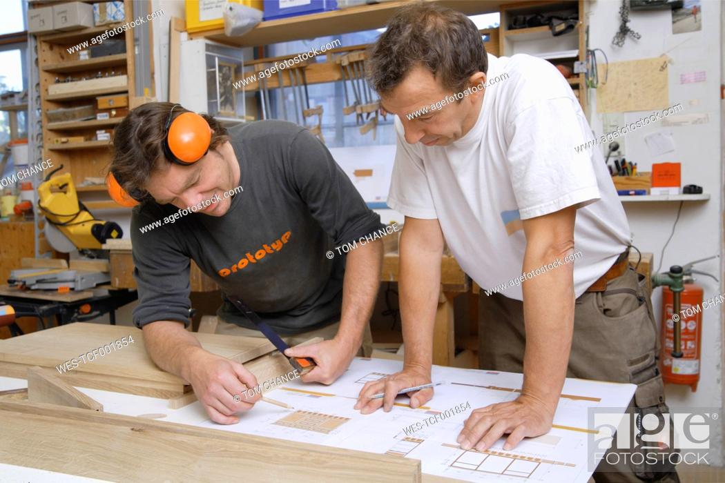 Stock Photo: Germany, Upper Bavaria, Schaeftlarn, Carpenters preparing blue print.